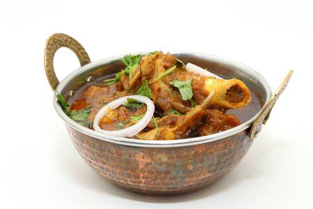 Plato de carne india o cordero al curry en un cuenco de latón de cobre. Foto de archivo