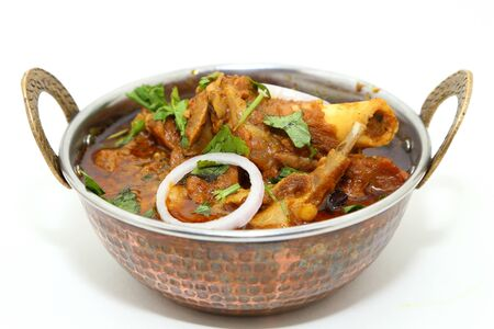Indian meat dish or mutton curry in a copper brass bowl.