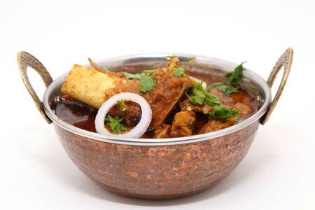 Plato de carne india o cordero al curry en un cuenco de latón de cobre.
