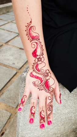 color tribal tattoo: Image detail of henna being applied to hand Stock Photo