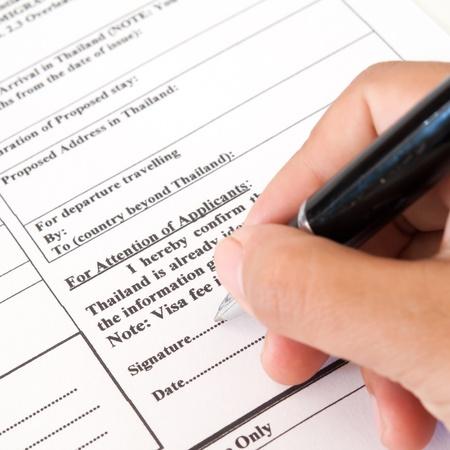 Llenar un formulario de solicitud de visado de entrada Foto de archivo