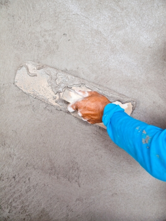 Close-up of hand using trowel to finish wet concrete wall