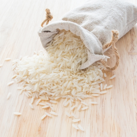 White long rice in small burlap sack photo