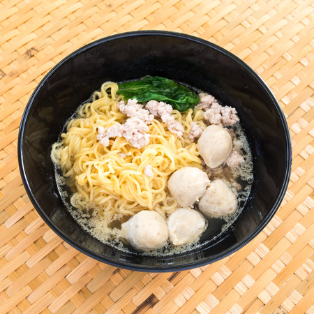 Eating instant noodle with minced pork and pork ball photo