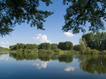 The light-blue sky with clouds and wood is reflected in the quiet river