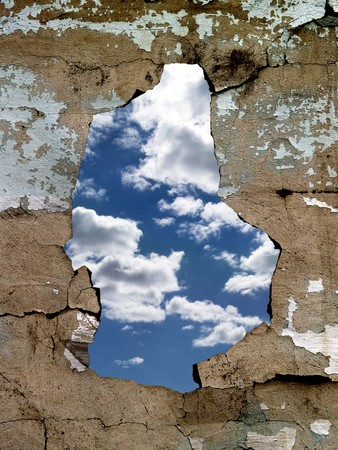 The hole in the cracked old wall, through which is visible the dark blue sky with clouds photo