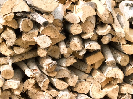 neatly stacked: armful of split firewood neatly stacked