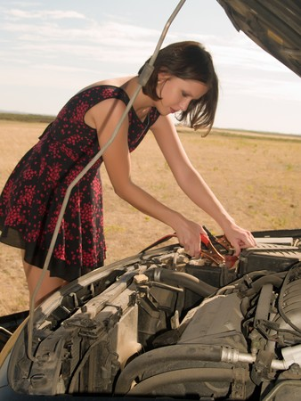 car battery: Young woman repairing car, connects cleats to the battery