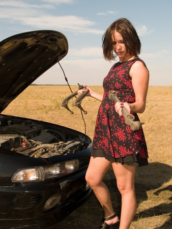 A beautiful young woman unsuccessfully trying to repair the car Stock Photo