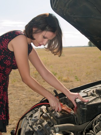 cleats: Young woman repairing car, connects cleats to the battery