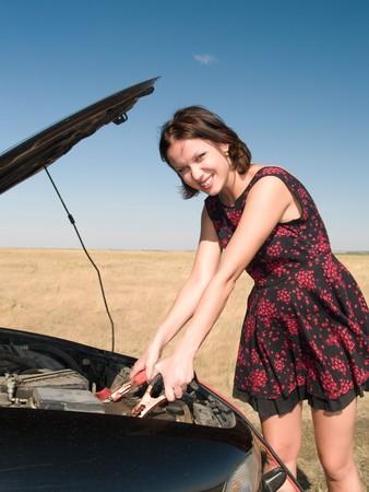 Junge Frau Reparatur Auto, verbindet Cleats mit der Batterie