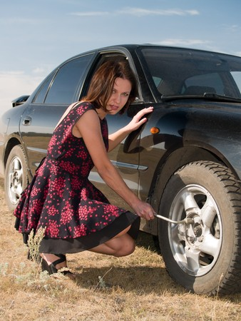 A beautiful young woman repairing a car, unscrew the wheel Stock Photo