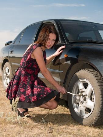 Eine sch�ne junge Frau Reparatur ein Auto, drehen Sie das Rad Lizenzfreie Bilder