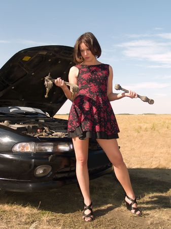 A beautiful young woman unsuccessfully trying to repair the car photo