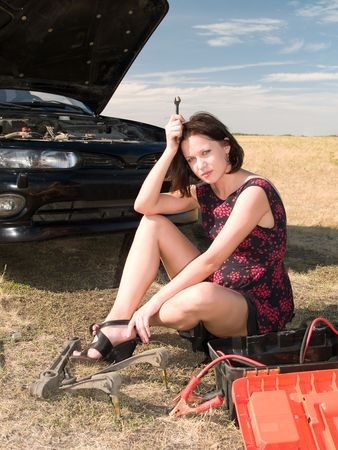 damaged: A beautiful young woman unsuccessfully trying to repair the car Stock Photo