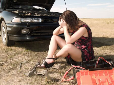 unsuccessfully: A beautiful young woman unsuccessfully trying to repair the car Stock Photo