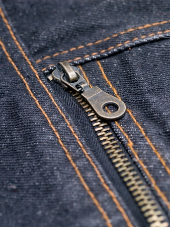 tight focus: buttoned zipper on dark jeans closeup Stock Photo