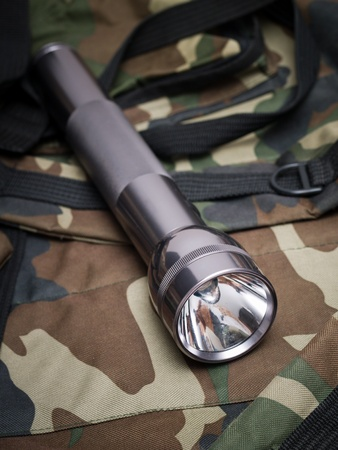 metallic flashlight on a backpack khaki