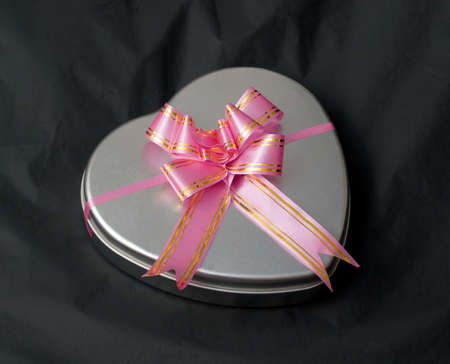 Gift box in the shape of a heart with a pink bow Stock Photo