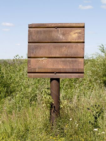 rusty signboard on a pillar, surrounded by green grass photo