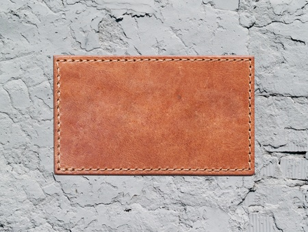 leather label sewn to the concrete wall photo