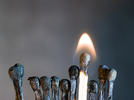 group of burnt matchstick and a one burning match  Stock Photo