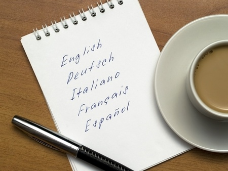 deutsch: multi-languages list in a notebook with a pen and a cup of coffee on a wooden background Stock Photo