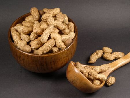 A cherry wood bowl and spoon of peanuts on a black background.
