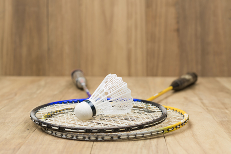 badminton: Shuttlecock and two racquets for badminton on a background of wood texture