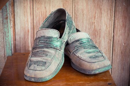 leather shoes: Dirty old leather shoes on wooden background.