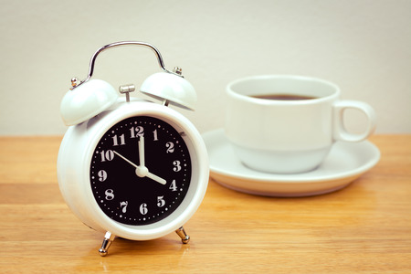 second meal: vintage alarm clock with coffee cup on the table