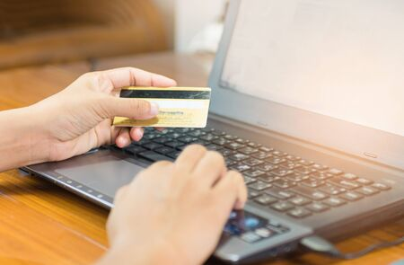 woman hand holding credit card and using notebook computer,payment and shopping online concept