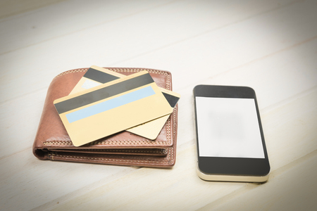 selective focus of gold credit card and smart phone on wooden table,retro tone