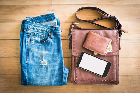 top view of blue plants jeans,brown leather bag and wallet with smarth phone on wooden background