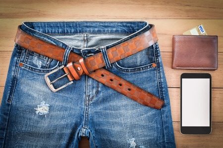 top view of blue plants jeans and wallet with smarth phone on wooden background