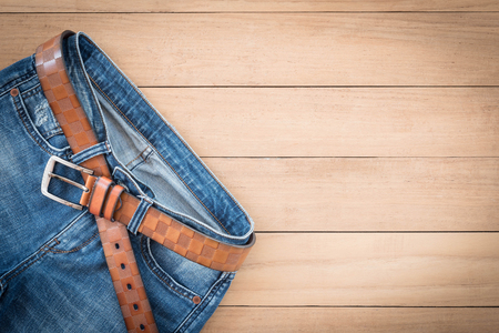 top view of blue plants jeans on wooden bakcground