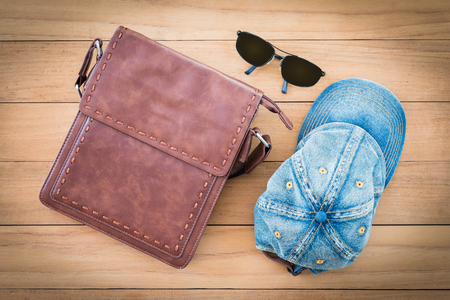 top view of brown teather bag and blue jeans cap on wooden background 版權商用圖片