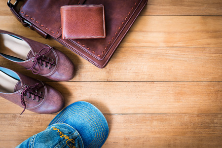 Top view image of womens fashion with leather bag,brown wallet,blue cap and shoes on wooden background.