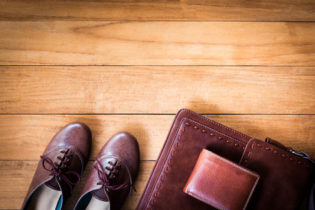 Top view image of womens fashion with leather bag,brown wallet and shoes on wooden background.