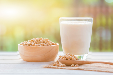 Soy milk in glass and soy been on spoon it on white table background with lighting in the morning,healthy concept.