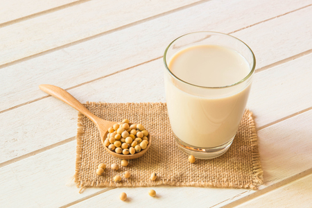 Soy milk in glass and soy been on spoon it on white table background,healthy concept. Archivio Fotografico