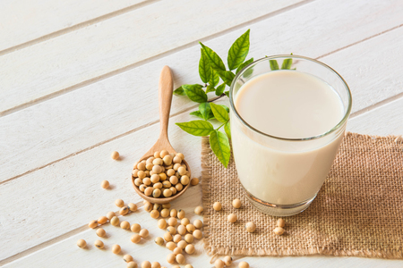 Soy milk in glass and soy been on spoon it on white table background,healthy concept. 版權商用圖片