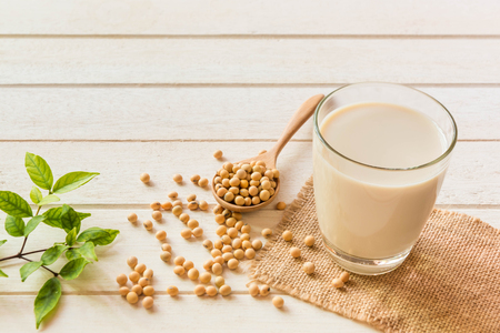 Soy milk in glass and soy been on spoon it on white table background,healthy concept. Imagens