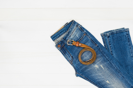 Top view of blue jeans and leather belt on white wooden background. 版權商用圖片