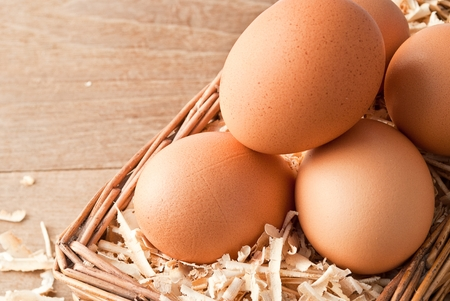 Egg on sawdust with old basket over on wooden background photo