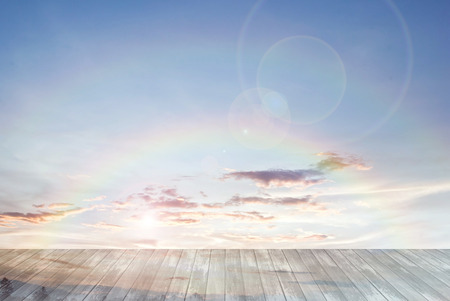 summer background: old wooden texture and rainbow with lens flare in blue sky background