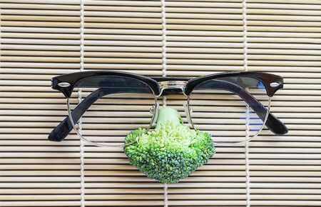 cruciferous: face of fresh broccoli with glasses on pattern bamboo for background Stock Photo