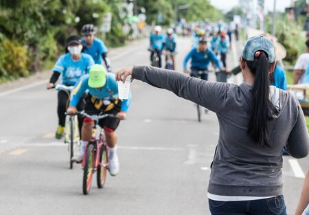 simultaneous: Lamphun,Thailand - August 16, 2015 : Public drinking water during on the way, a powerful combination, event Bike for mom from Thailand, event respected to Queen Sirikit and thailands cyclists record for worlds