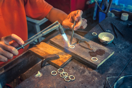 silversmiths hands while working making jewelry.