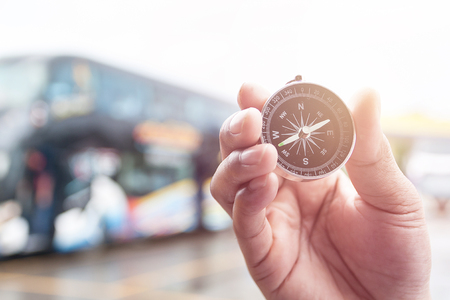 compass: Compass in hand on blur of bus for background